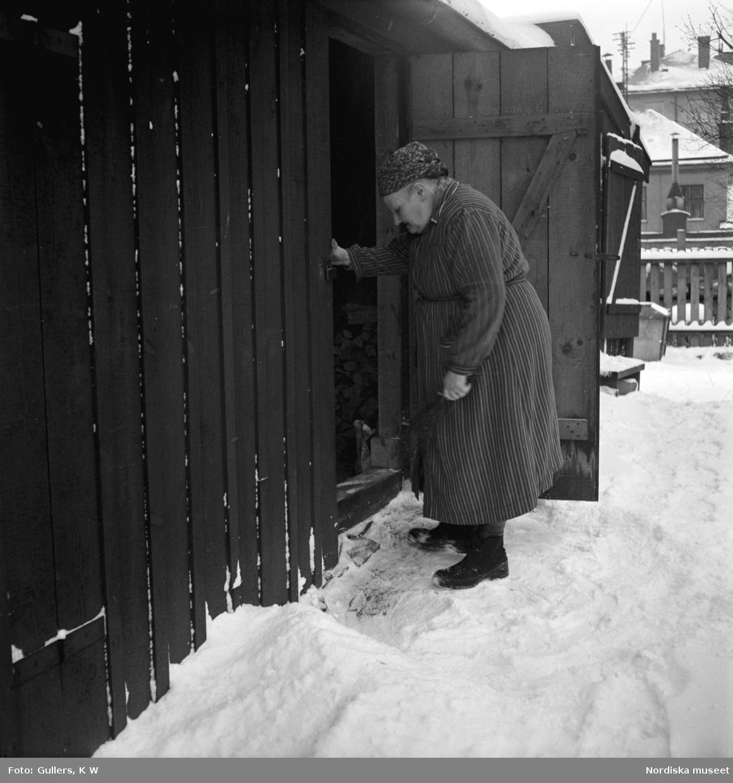 """""""En gammal kvinna har mödosamt skottat en smal gång från sin dörr efter nattens snöfall."""" Högalid, Södermalm, Stockholm."""
