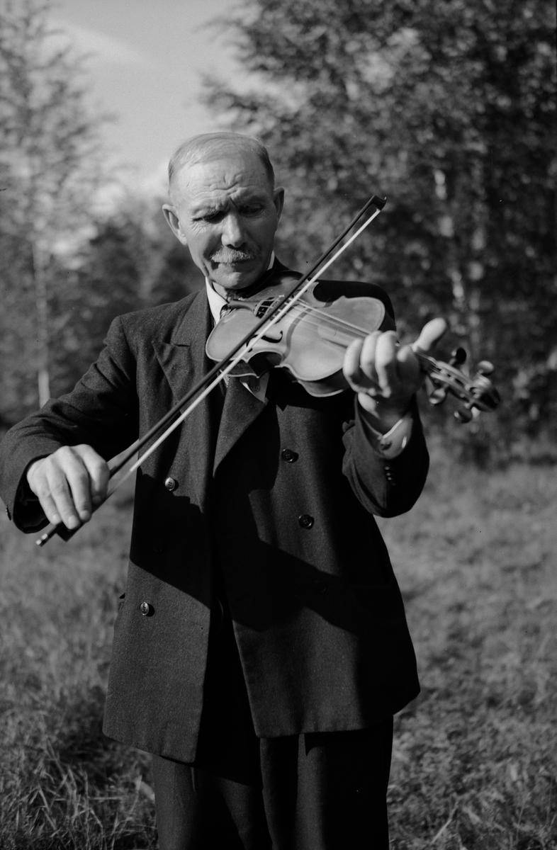 Spelman med fiol vid spelmanstävling i Granebergsparken, Sunnersta, Uppsala augusti 1945