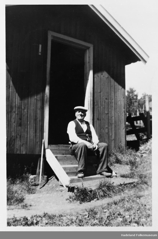 Kristian Guttormsen sitter på trammen til sitt hjem, Molid stua. Her bodde han på et rom med 10 unger.