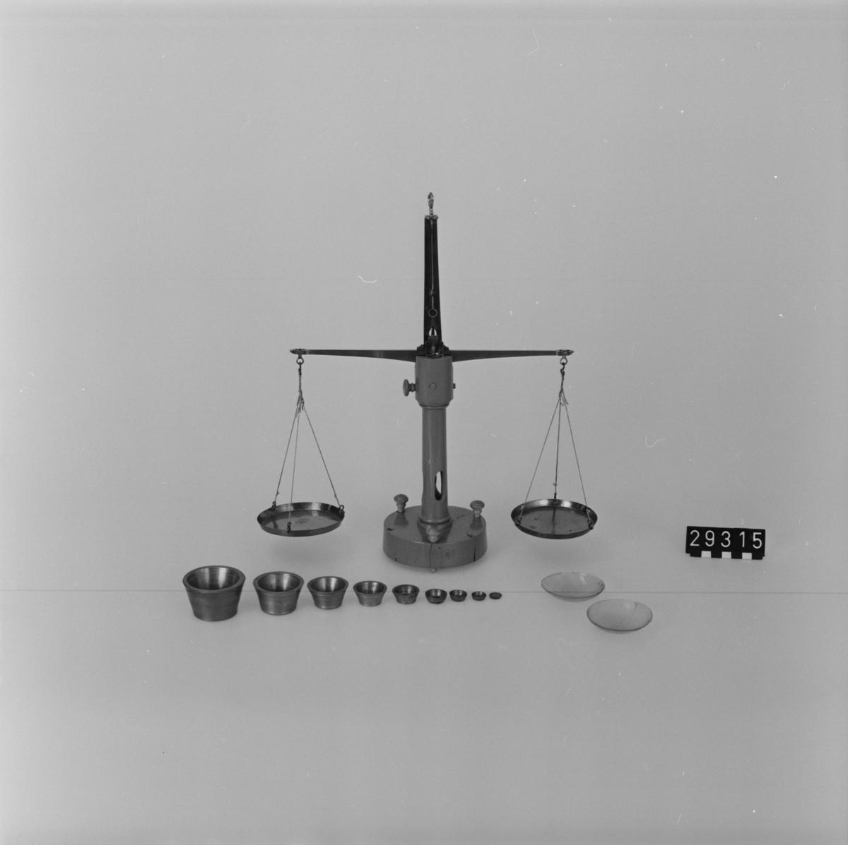 Probervåg med likarmad balans av järn (apoteksvåg) i etui med svart läderklädsel. Etuiets längd: 300 mm, bredd: 210 mm, höjd: 70 mm.