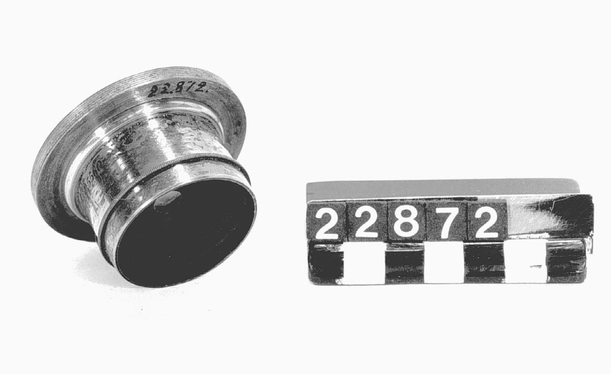 Bälgkamera av trä, för plåtar 13 x 18 cm. Thornton-Pickard ridåslutare. Jämte tillbehör, i två tygväskor. 6 st insticksbländare i etui av läder 6 st träkassetter Stativ av trä Ett litet objektiv     Steinhein Muncchen NO 25560 i läder etui Ett stort objektiv    C.Böhmke & Co Braunschnveig NO 322 i läder etui Extra objektivplatta Wertninkel aplanat 7 mm Tillbehör: Kamera, större objektiv (C. Böhmke & Co, Braunsschweig, nr. 322) med objektivlock och fodral av läder, 6 insticksbländare till dito, i etui av skinn, mindre objektiv, vidvinkelplanat (Steinheil, München, nr. 25560) med roterande skivbländare samt lock och fodral av läder, objektivbräda till dito, reduktionsmutter för objektiv, stativhuvud av mässing, 6 dubbelkasetter av trä, fodral av smärting, med skinnskodda sömmar, till kameran, dito till kasetterna.- 3 stativben av trä, till ovanstående huvud. (ink. nov. 1953.).
