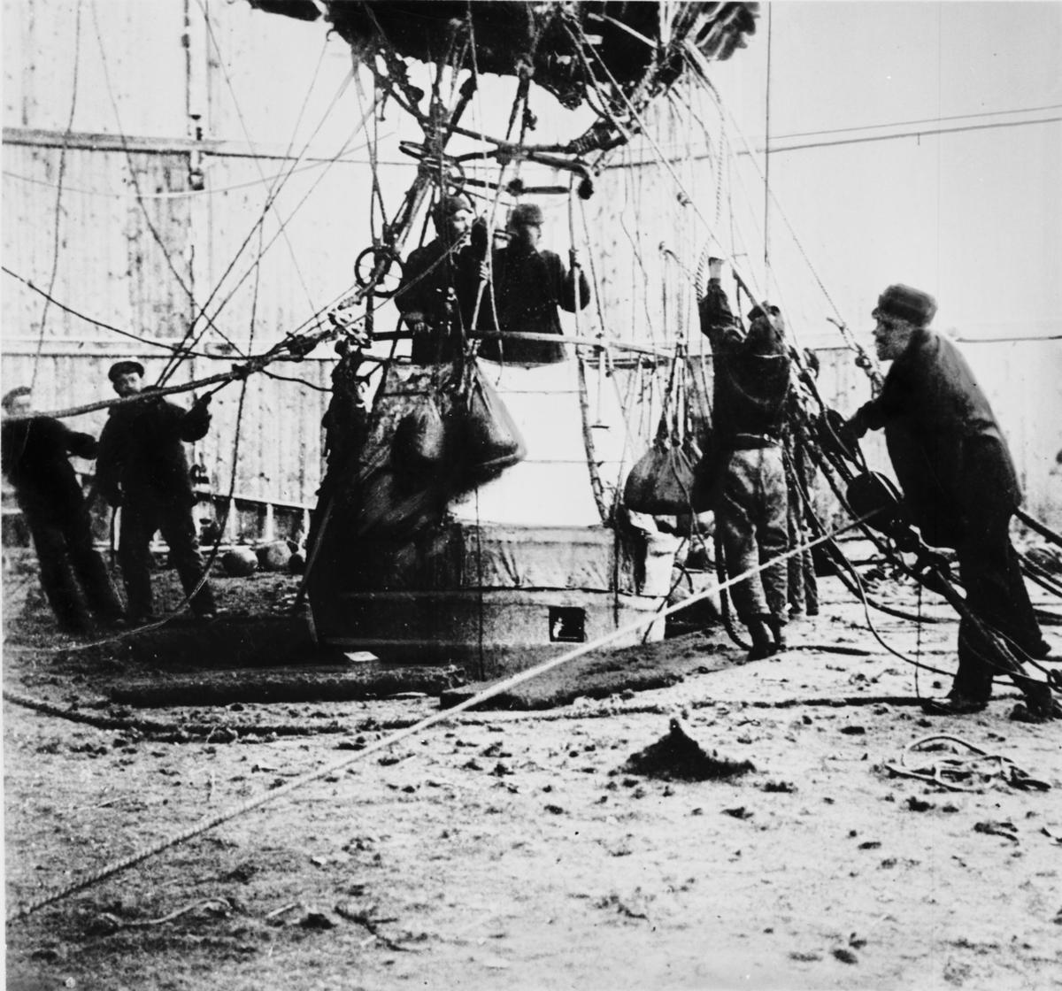 Någon minut före starten. I gondolen står Andrée längst till vänster, bredvid honom Strindberg. Mellan dem skymtar Fraenkels rygg och nacke.