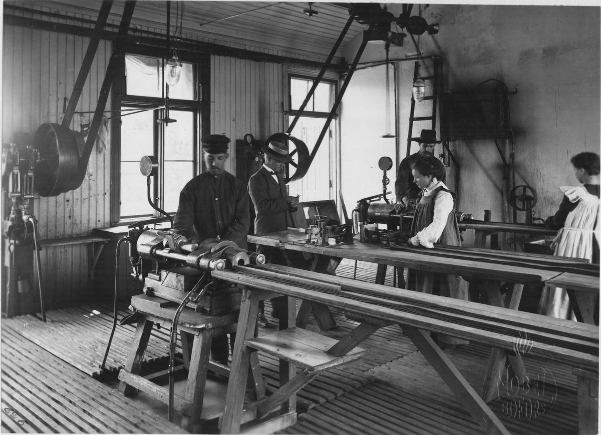 AB Bofors Nobelkrut. Tillverkning av nobelkrut (ballistit). Krutmassan, utstansad till skivor lagom för pressarna, formas här till långa rör (maccaronikrut). Pressarna är uppvärmda och trycket på massan mycket högt (6 a' 700 atm).