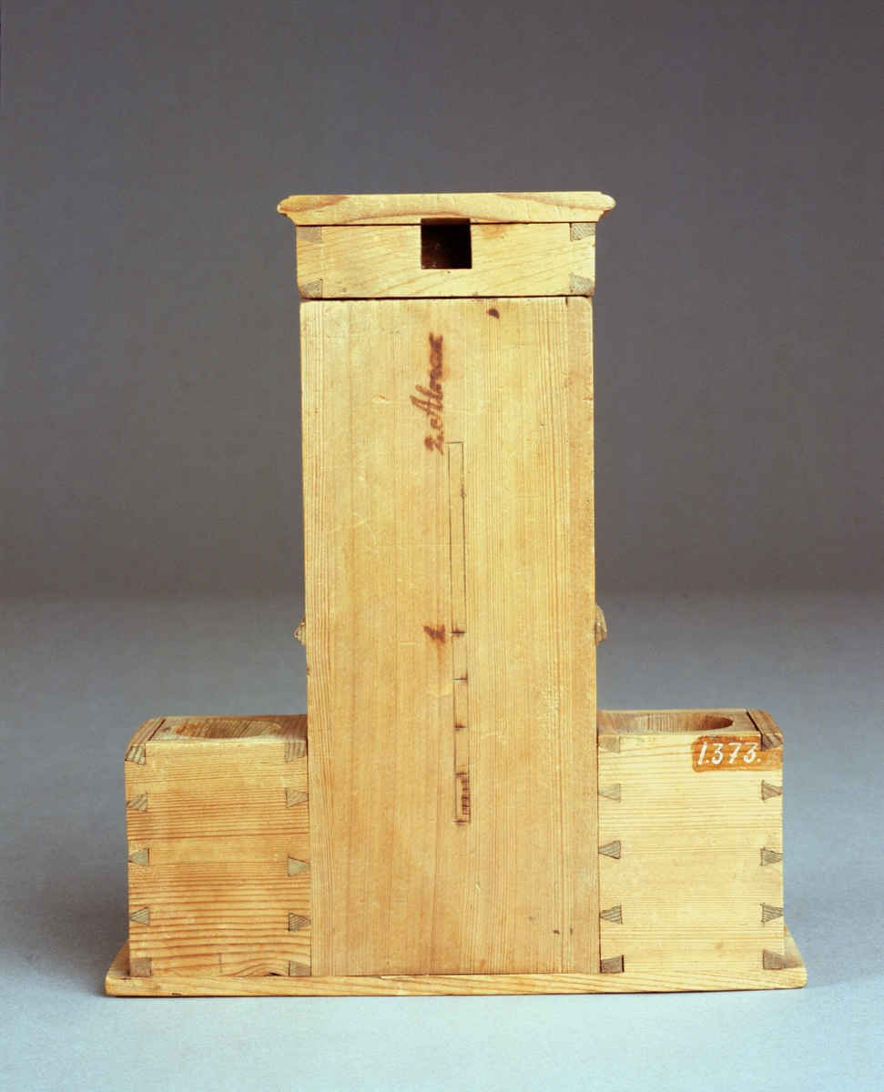 """Modell av kakelugn. Text på föremålet: """"D.b.B.9 Tab. IX.b"""". I Jonas Norbergs förteckning från 1779 beskrivs modellen på följande sätt: """"Modell på mur omkring en bryggpanna, hvarss hela [... ] elden genom ledningar och drag tvingas at omfara, til befordran af snäll upkokning med litet ved."""""""