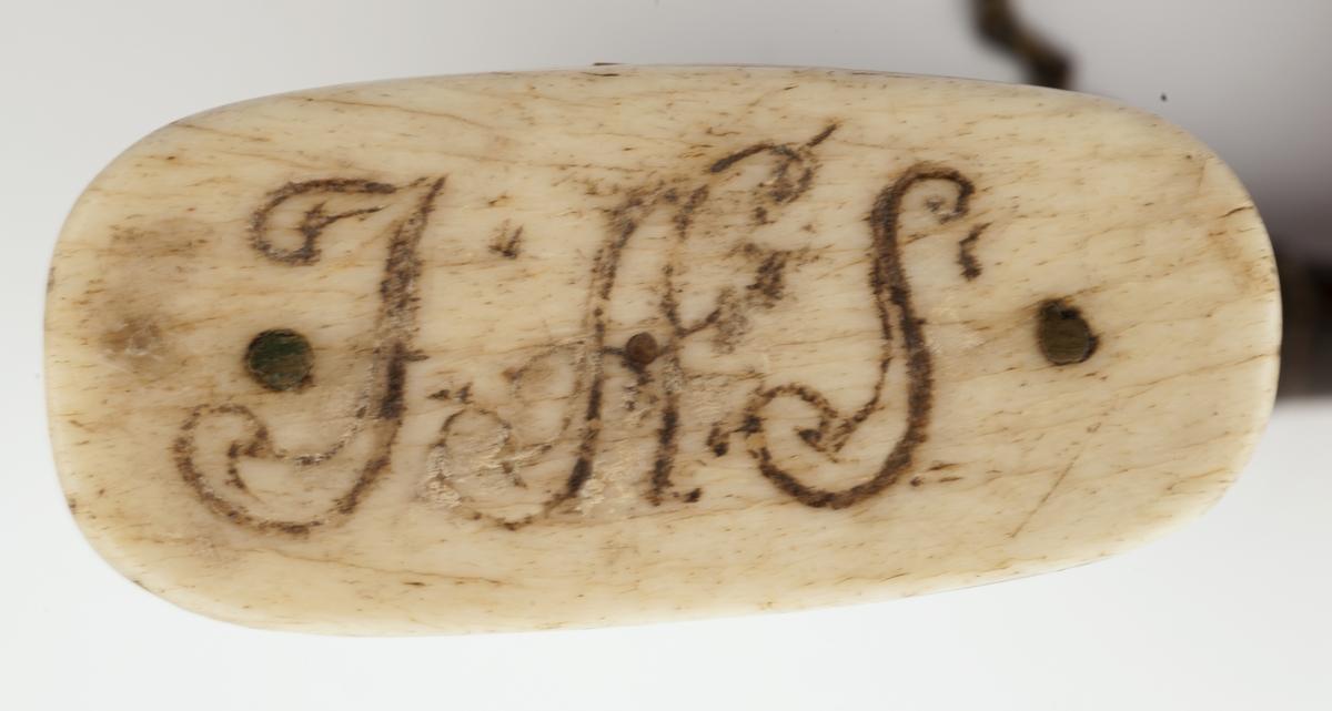 Mindre krutthorn med flat bunnplate i tre og bein med innskrift. Messingsbeslag ved tuten med en kjede til proppen (som mangler). Ornamentikk på horn i form av blomster i en vase på begge sider og bårder på kantene.