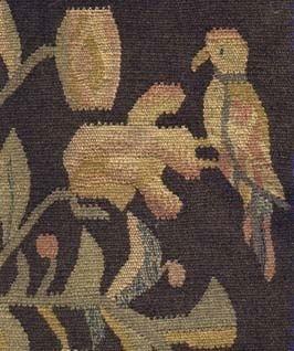 Rölakans-kudde vävd i inslagsrips med blå bomullsvarp och ull som inslag. Baksidan är helt enfärgad, brunmelerad. Framsidan är mönstervävd i olika nyanser av brunt, grönt, gult, rött, blått och naturvit.  Kudden är ihopsydd på tre sidor och saknar innerkudde.