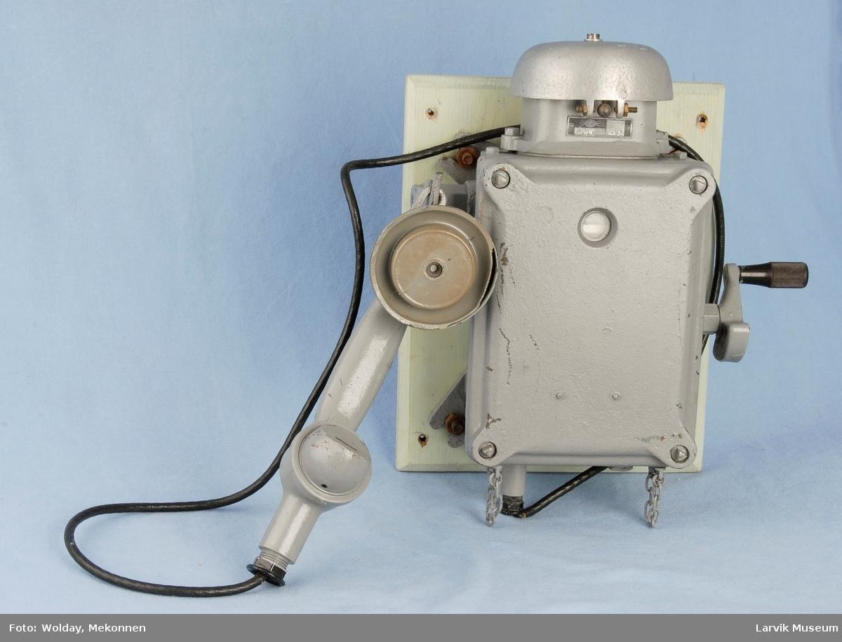 Form: Telefon for veggmotasje m/oppheng for telefonrør på siden. Sveiv på andre siden. Bjelle på topp