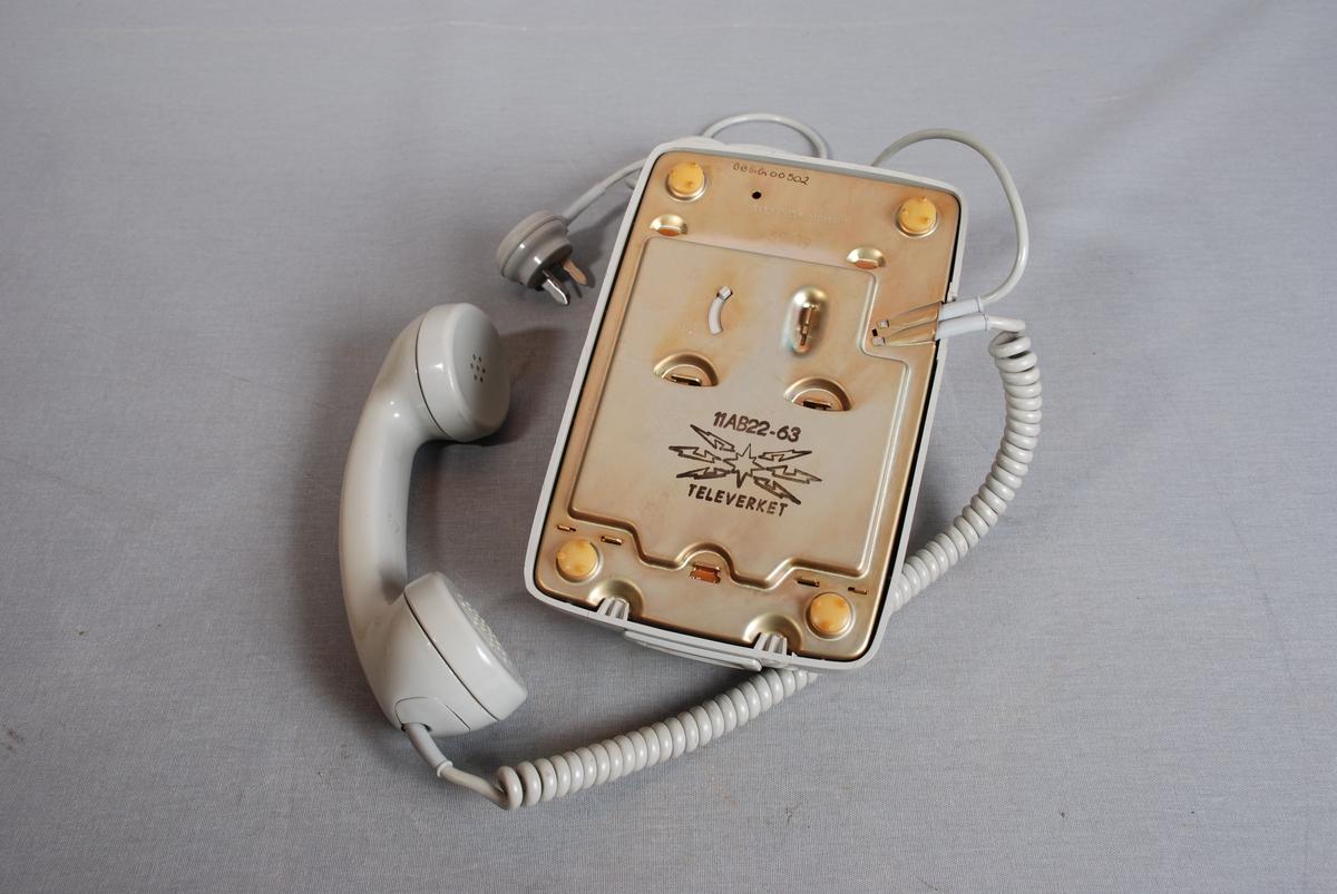 Telefonapparat med tallskive, telefonrør på gaffel som bryter kontakten når røret legges ned på gaffelen. Spiraltvunnet ledning mellom apparat og telefonrør. Telefonledning med trepolt støpsel i enden.