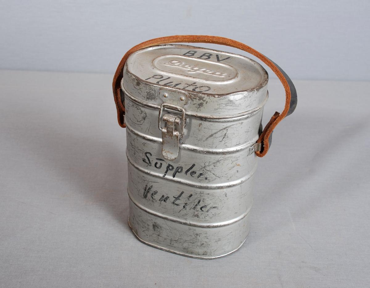 Sylindrisk metallboks med ovalt tverrsnitt, hengslet flatt lokk med lukking og lærhank. flat bunn. På undersiden av lokket er det et firkantet metallrom med lokk, for oppbevaring av linser.