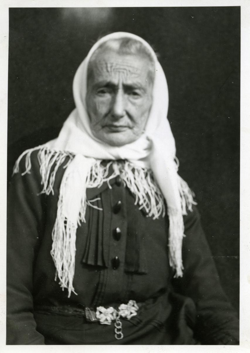 Portrett av eldre kvinne . Hun er kledd i mørk kjole med knapper foran, belte med blank beltespenne og lyst skaut på hodet.