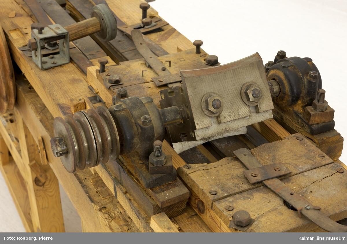KLM 45520:108. Stavhyvelbänk, stavhyvelmaskin, trä, metall. Arbetsbänk med flera tillbehör och funktioner, ombyggd och tillbyggd efter behov. Med glidbana av järnband för stav (till tunnor) som hyvlas med två olika hyvelstål, konvex och konkav egg, på både insidan och utsidan. Staven matas fram på länkad kejda som kan justeras efter brädans längd. Brädans bredd kan justeras med bultar och spår på järnbandet. Bänkens funktioner har drivits med band- och kilremmar som kopplats till en motor. Ett flertal lösa, utbytbara delar till bänken finns. På bänkens trästomme syns tydliga spår, i form av utskurna partier och märken, efter lager, axlar och bultar. Bänken är inte komplett, utan har ursprungligen varit större och har troligtvis haft fler funktioner och maskiner knutna till sig. På bänkens ena hörnstolpe hänger en fast nyckel.