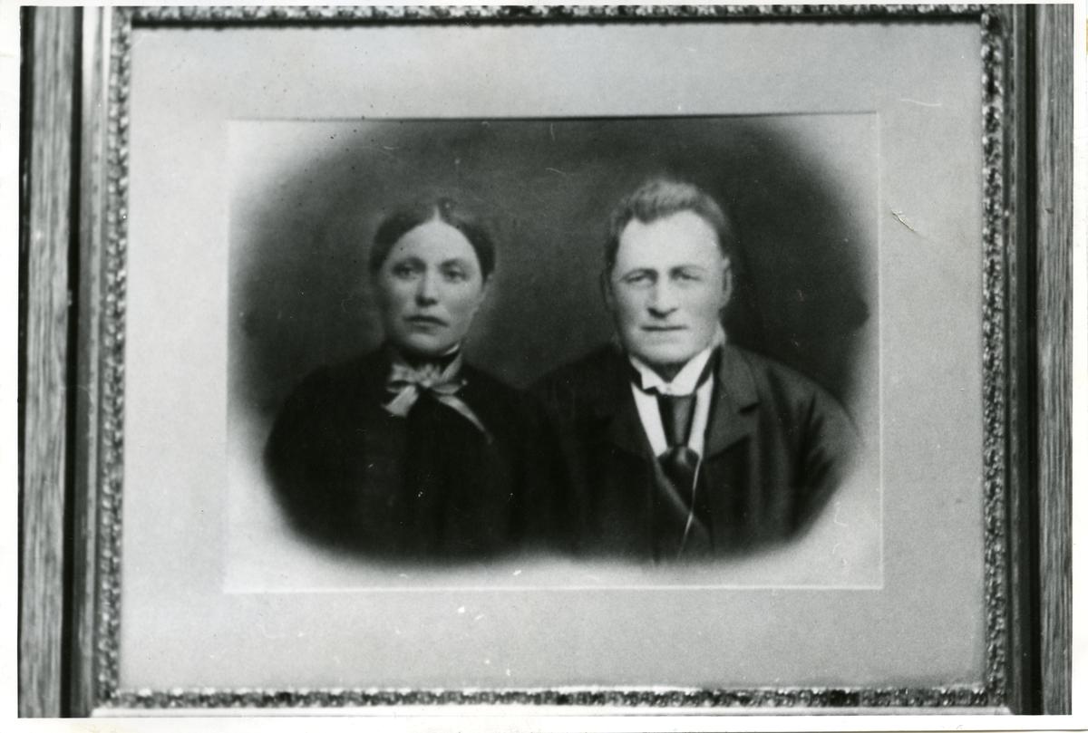 Porterett av en kvinne og en mann. Kvinnen er iført en mørk kjole med halstørkle og mannen er iført skjorte med slips og en mørk frakk over.