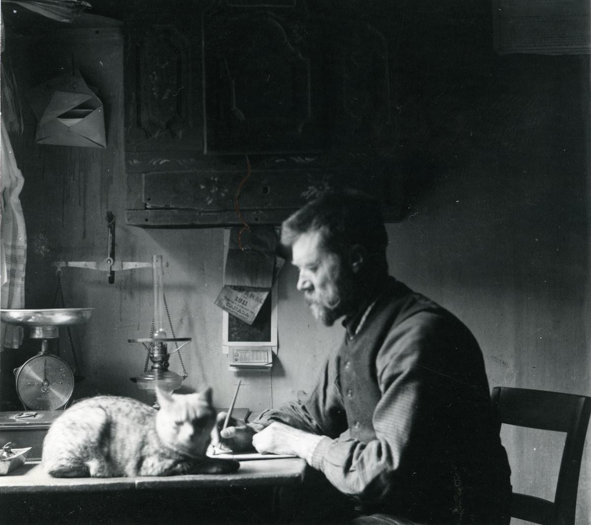 Mann sittende ved et skrivebord. En katt ligger ved hans side.