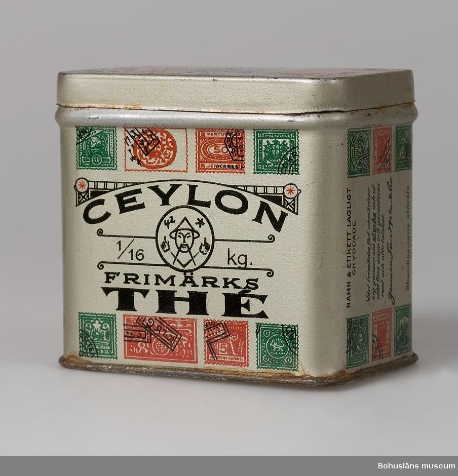"""Framsidan märkt: """"Ceylon 1/6 Kg Frimärks THE"""". Dekorerat med gröna och röda frimärken. Asken märkt i botten: """"Lundgrens Theer alltid bäst"""". Baksidan av burken märkt: """"Lundgrens Äkta Frimärks The"""", """"Utvalt från de förnämsta trädgårdarna på Ceylon""""."""