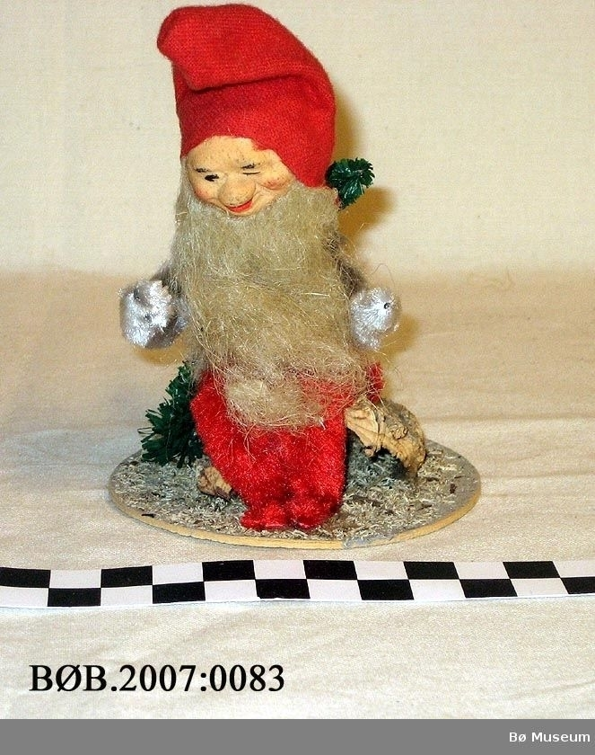Julenisse som sit på ei rot. Nissen er laga av piperenserar. Han har skjegg og raud luve. To små grantre. Alt er festa på ei rund pappplate.