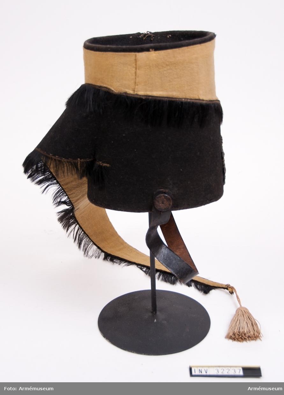 Grupp C I. Ur paraduniform för manskap vid Livgardet till häst 1820-45. Består av dolma, byxor, husarmössa, plym, pompong, stövlar, sporrar, spännhalsduk, knutskärp, kartusch, kartuschrem, handskar, fodermössa, sabelkoppel, sabeltaska, remmar, sabel, balja, sabelhandrem. Husarmössa go 2/3 1820.