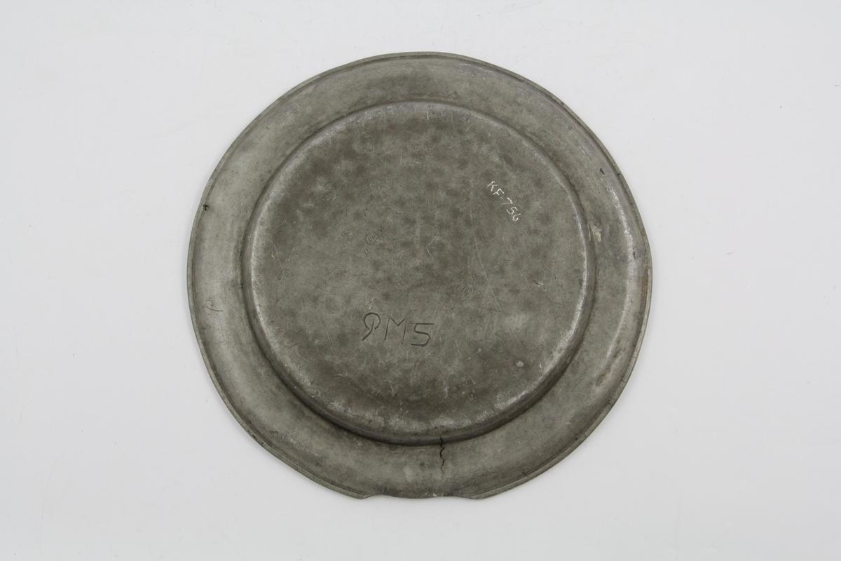 Flat, tinn, sirkelrund, kant med oppbøyet rand prydet med gravert linje. Baksiden stemplet to steder, men stemplene er nesten utviskede.