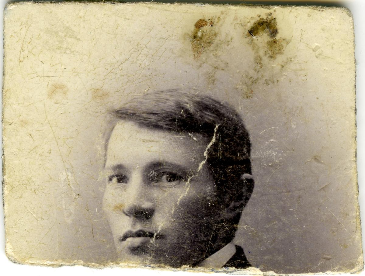 Deler av portrett av ukjent mann. Fotografiet er i dårlig forfatning og man kan bare se øvre halvdel av portrettet.