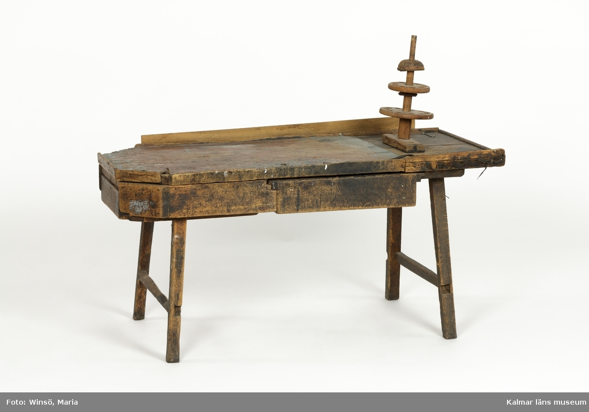 KLM 45466:3. Arbetsbord, skomakarbord. Av trä. Lågt, rektangulärt bord med fyra ben. Två av bordets hörn är avfasade. En utdragbar låda vid ena kortsidan, samt vid långsidan en större låda som kan dras ut från båda sidor. Bordsskivan är till största del täckt med ett stycke säckväv som är fläckad av brun och grå färg. På bordet sitter ett verkstygsställ med olika avsatser, varje avsats består av en rund träskiva med hål, för placering av verktyg. Den bakre långsidan har en påspikad bräda. På bordets främre del, till höger, en läderrem som spikats fast som öglor och som det avses sättas verktyg i. På bordsskivan en fastskruvad läderrem, en hasp och en ögla av järn. Väl använd.