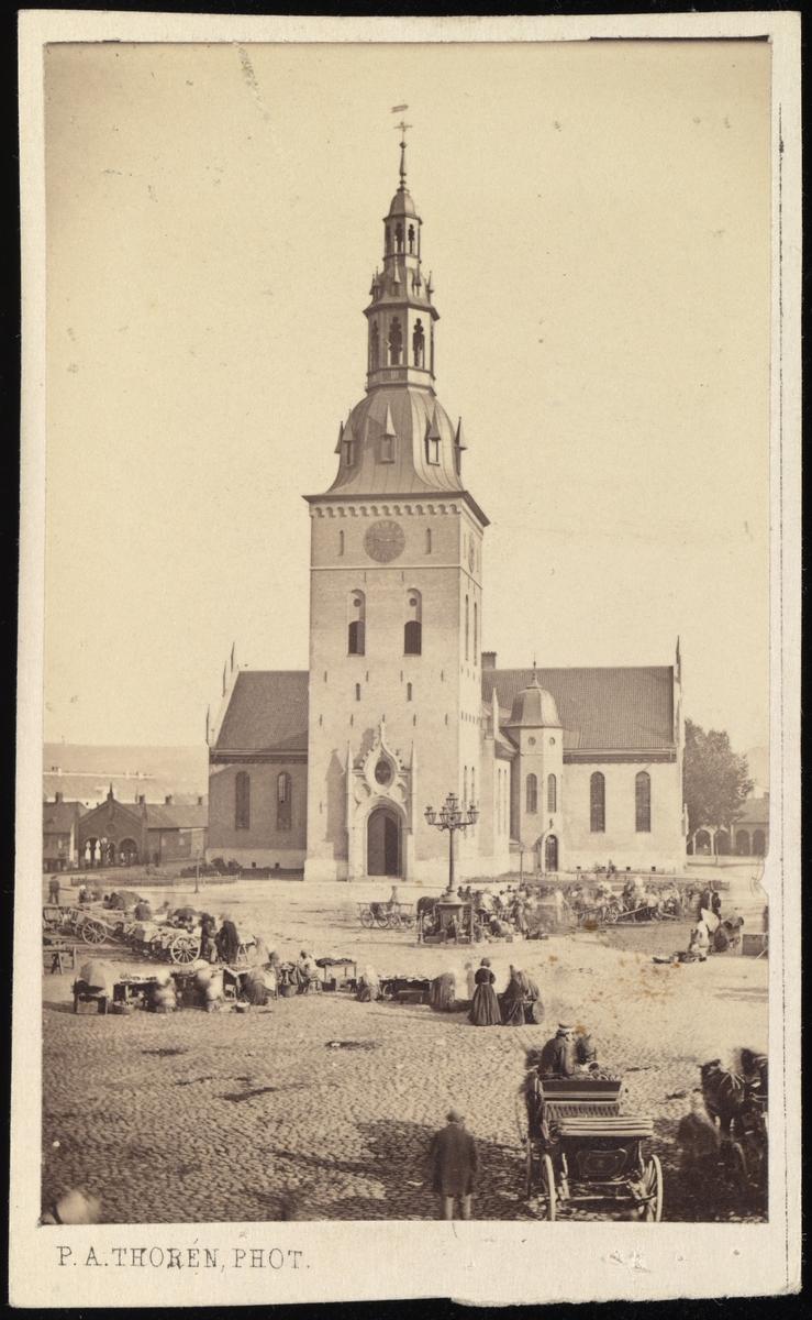 Bilde av Oslo Domkirke sett fra Stortorget, som er fullt av folk og salgsvogner.