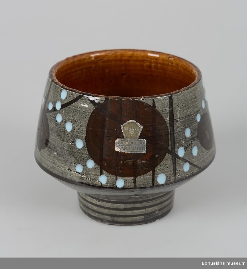 Rund. Rak kant, avsmalnande uppåt. Kanten gör en vinkel ner mot en klack som vasen står på. Brun blank glasyr på insidan. På utsidan är det en ojämt grå botten med dekor i brunt, svart, och ljusblått. Dekoren är i form av rundlar, prickar och ränder. Firmaetikett.