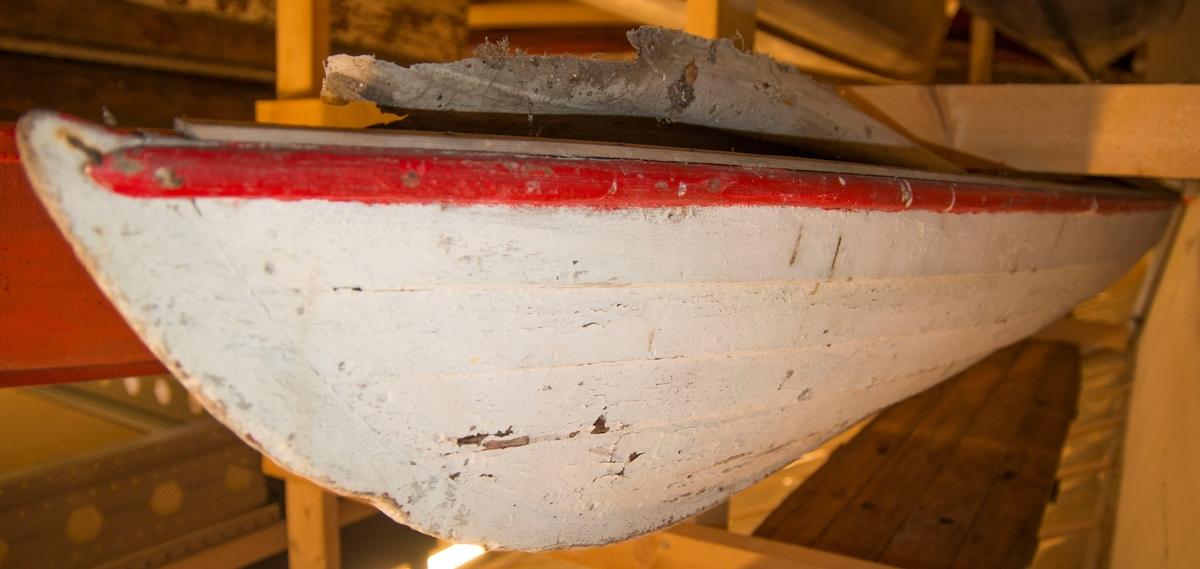 Kajakk av tre. Klinkbygd med seildukstrekk. Furu. Hvit med rød list. Fem bordganger.