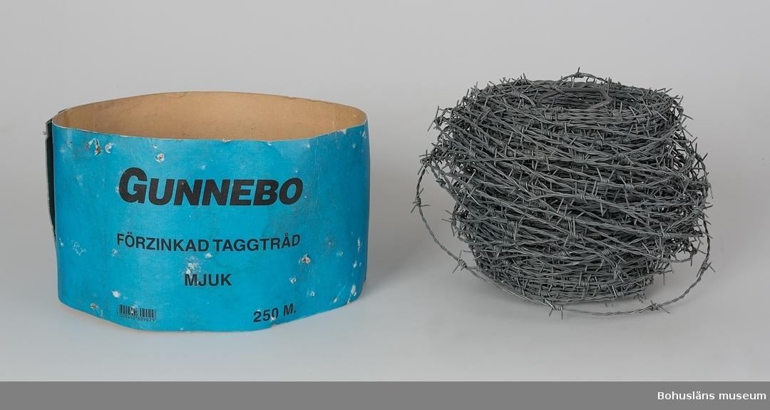 Rulle av galvaniserad taggtråd med ett bärhandtag i mitten. Originalemballage av blå kraftig papp med påtryckt text: GUNNEBO FÖRZINKAD TAGGTRÅD MJUK 250 M