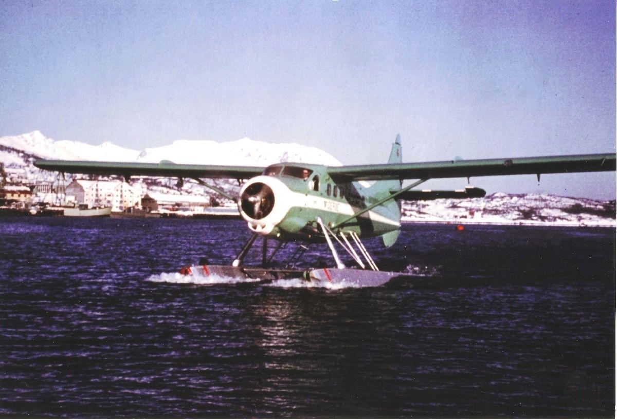 Havnebasseng. Harstad. Et fly, DHC-3 Singel Otter fra Widerøe, taxer inn mot brygga i sjøflyhavna. I bakgrunnen Harstad sentrum og Trondenes.