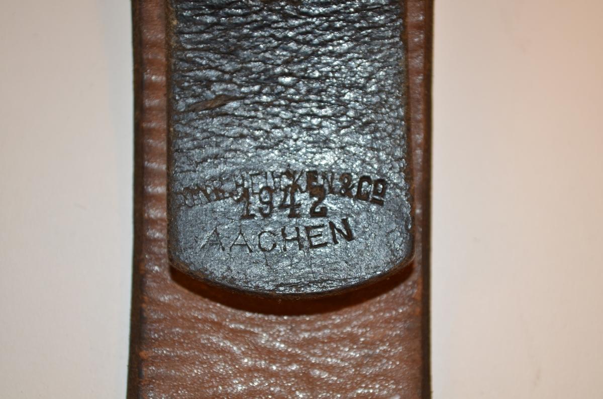 """Brunsvart belte tilhørende uniform brukt av den tyske okkupasjonsmakten i Norge under andre verdenskrig. Beltet er av lær med beltespenne i metall. Emblemet med den tyske ørn og hakekors er skrapet bort fra beltespennen. Stempel på innsiden av læret, hvor """"Aachen 1942"""" kan tydes. Varemerke utydelig."""