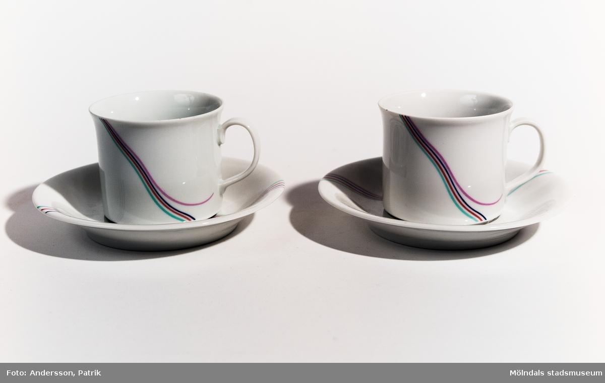 Två par kaffekoppar med öron och tillhörande fat. Modellen kallas Rainbow och är designad av Bertil Vallien. Tillverkad av Rörstrands under 1980-talet. Grundfärgen är vit och snett över både kopp och fat löper fyra smala, parallella slingor bestående av färgerna grön, röd, mörkblå och rosa. Den sista rosa är formad som en sväng bort från de andra slingorna.