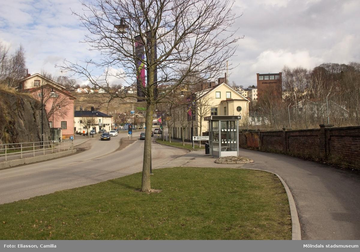 """Kvarnbygatan i riktning mot öster. I bildens mitt ses Gamla Torget till vänster och Kvarnbygatan 4 (Byggnad 231) till höger. Gatan går förbi f.d Papyrus-områdets mur till vänster. I samband med denna fotografering pågick en 80-talsutställning på Mölndals stadsmuseum, 17 maj 2014 – 4 oktober 2015, vilket syns på vimplarna vid busskuren/hållplatsen """"Gamla torget"""". Längre fram (ej i bild) börjar backen """"Kråkan"""". I vyn till vänster ser man Gamla torget och ovanför detta nya Kvarnbyterrassen som bebyggs med bostäder. Den höga byggnaden till höger är Stora Götafors."""