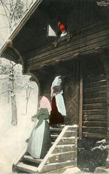 Kolorert postkort. To kvinner på trappa foran stabburet. Lit