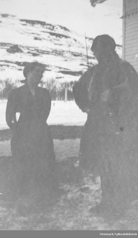 Fredenslund, pinsen 1917. Kvinneskikkelse i mørk kjole, eller bluse og skjørt i konversasjon med en mann kledd i et pelslignende ytterplagg, muligens en samisk pesk. Det er april 1917 (pinsen). Fredenslund var Lensmann Strands gård, og lå i Bonakas, Tana. Bonakas, nordsamisk: Bonjákas, er en jordbruksbygd beliggende på vestsiden av Tanaelva i Tana kommune omkring ti kilometer ovenfor Tanamunningen.