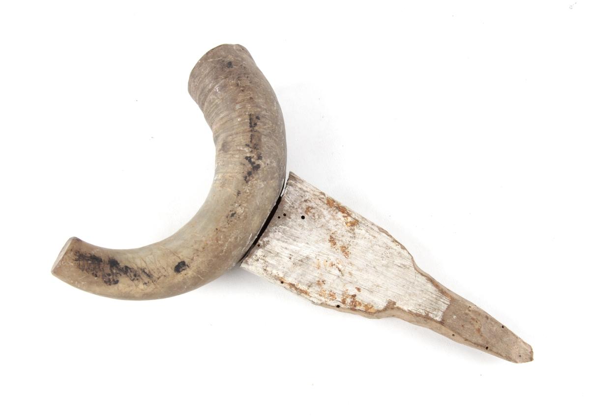 Vadbein av kuhorn, med trekantformet tretapp til å feste i båtripen. Kuhornet har naglet på et lokk i den største enden og en tapp på hornspissen.