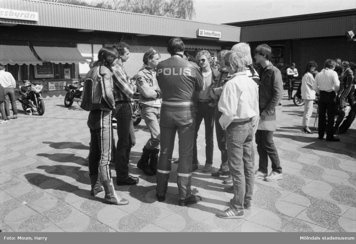 Kållereds Motorklubb visar upp motorcyklar i Kållereds centrum, år 1984. MC-polis Lennart Johansson samtalar med en samling killar.  För mer information om bilden se under tilläggsinformation.