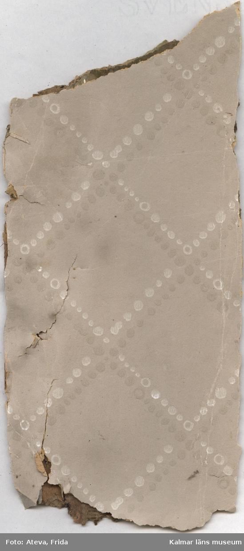 KLM 44059. Tapet av papper. Tapetbit med flera olika tapetlager. Överst en tryckt tapet med grå botten och diagonalt rutmönster bestående av vita och grå prickar. Underliggande lager har mönster med putsimitation, 1930-1940-tal. Nästa lager har tryckt mönster med bruna och mörkgröna diagonala rutor. Blommor i trycket i ljusgrönt, 1920-tal(?). Nästa synliga underliggande lager har tryck i rött och grönt på ofärgad botten. Nästa lager har tryckt mönster med svarta och vita vågräta linjer i lodräta fältindelningar. Röda blekta detaljer. Lagret under har tryckt mönster i svart på ofärgad botten. Nästa lager har diagonala rutor i ultramarinblått med ultramarinblåa prickar mellan. Allt på ofärgad botten. Fler underliggande lager vars mönster inte går att se. Övre lagret daterat till 1950-1960-tal.
