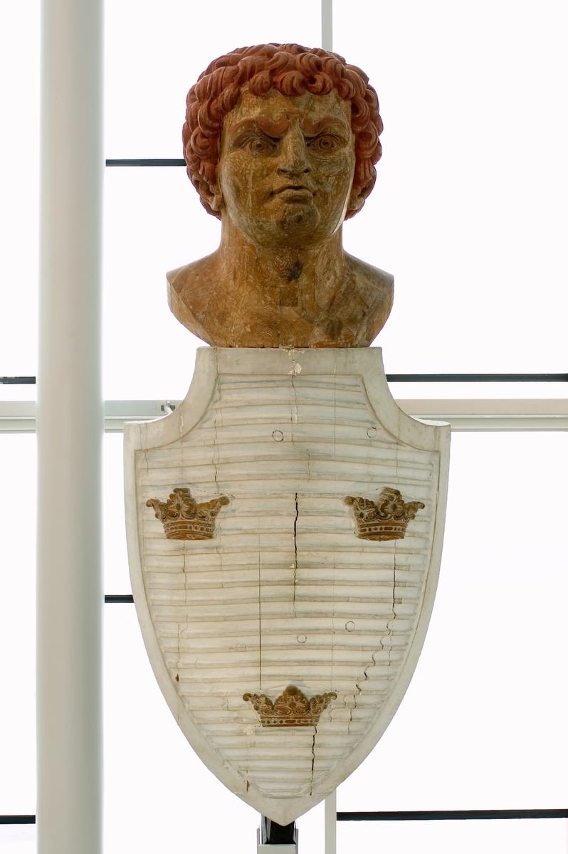 Galjonsbild tillhörande linjeskeppet Dristigheten. Huvud av mansperson med lockigt hår fäst ovanpå en sköld med tre kronor. Färg: omålad med hår och ögonbryn röda. Skölden är vit.