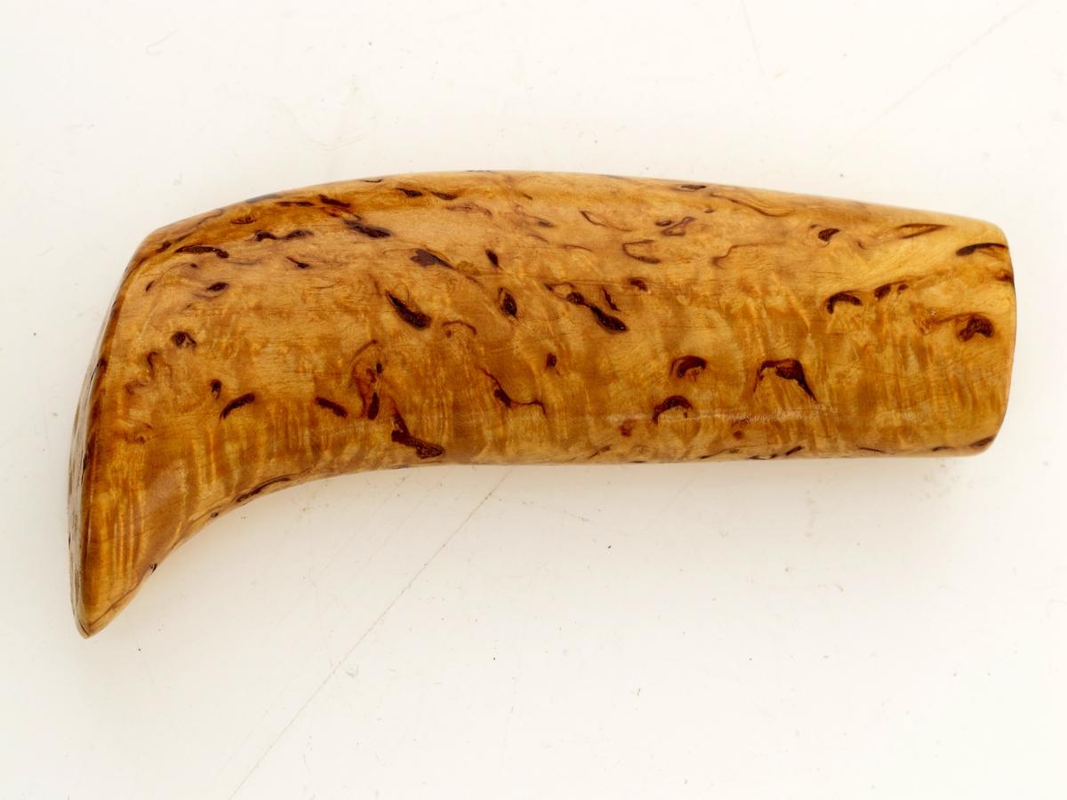 Knivskaft  av valbjørk, lakket. Ubrukt - ikke montert på knivblad.  Skaft med ovalt tverrsnitt. buet i enden, og med en svakt buet, oval endeflate.