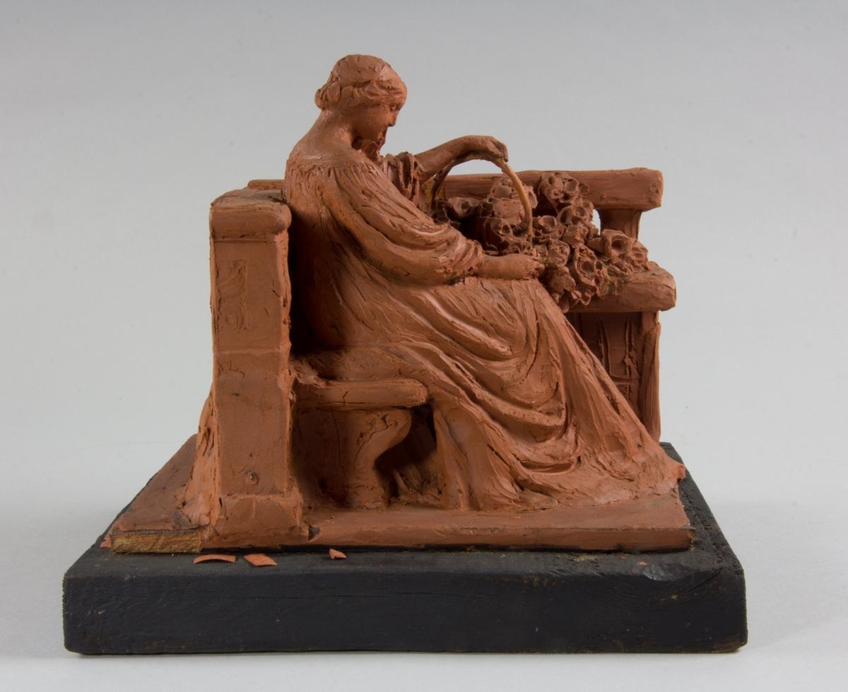 En ung kvinna, helfigur, i lång klänning. Hon sitter på en bänk och bredvid henne en rosenkorg. Arkitektonisk omgivning.