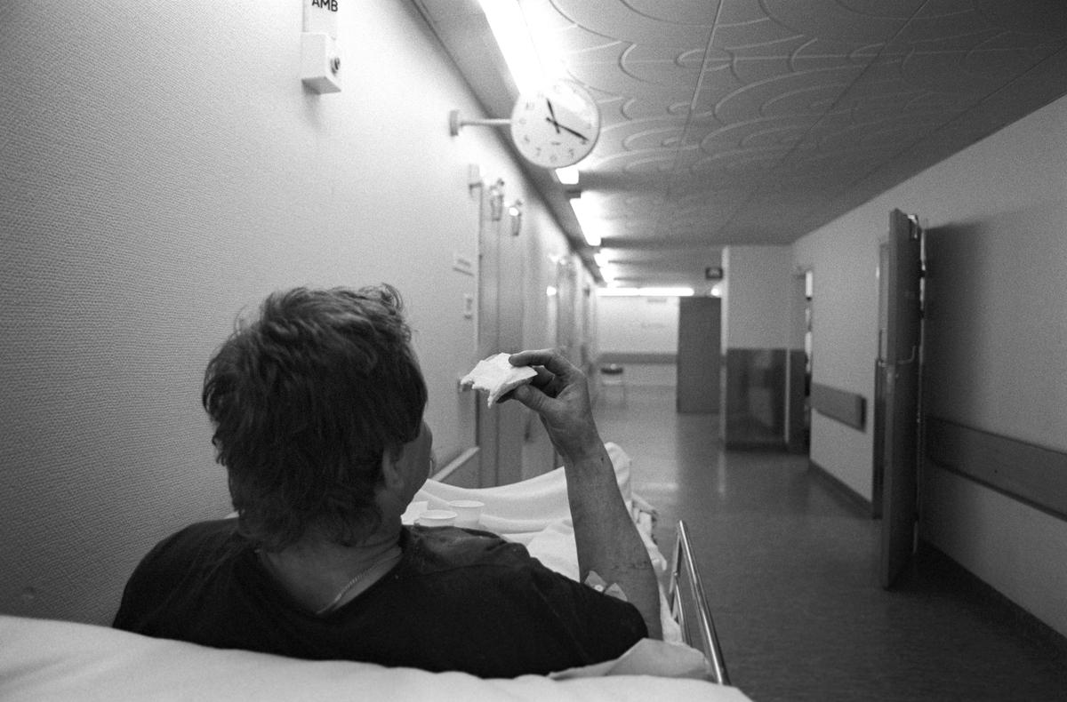 Patient liggandes i korridor äter smörgås, Akademiska sjukhuset, Uppsala 1991
