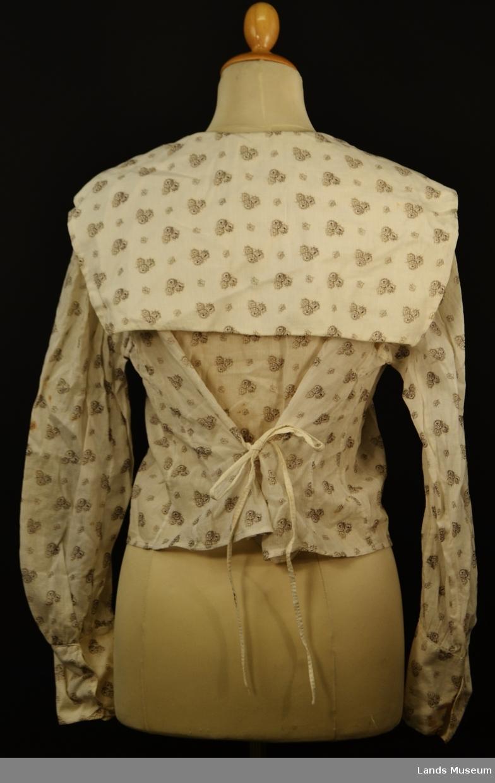 Bluse med matroskrage og lang arm med brede mansjetter. Bomullstoffet er mønstret med rosebuketter i grått og svart. Knyting bak i ryggen.