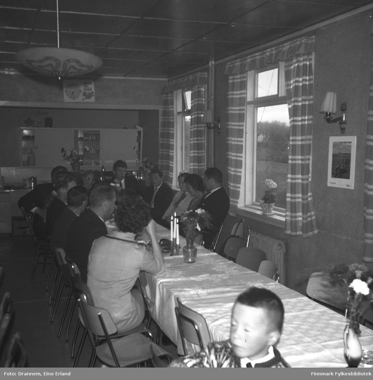 Mange personer sitter ved et langbord i et lokale i Neiden. Dette kan være fra Alfred Karikoskis begravelse i august 1965.