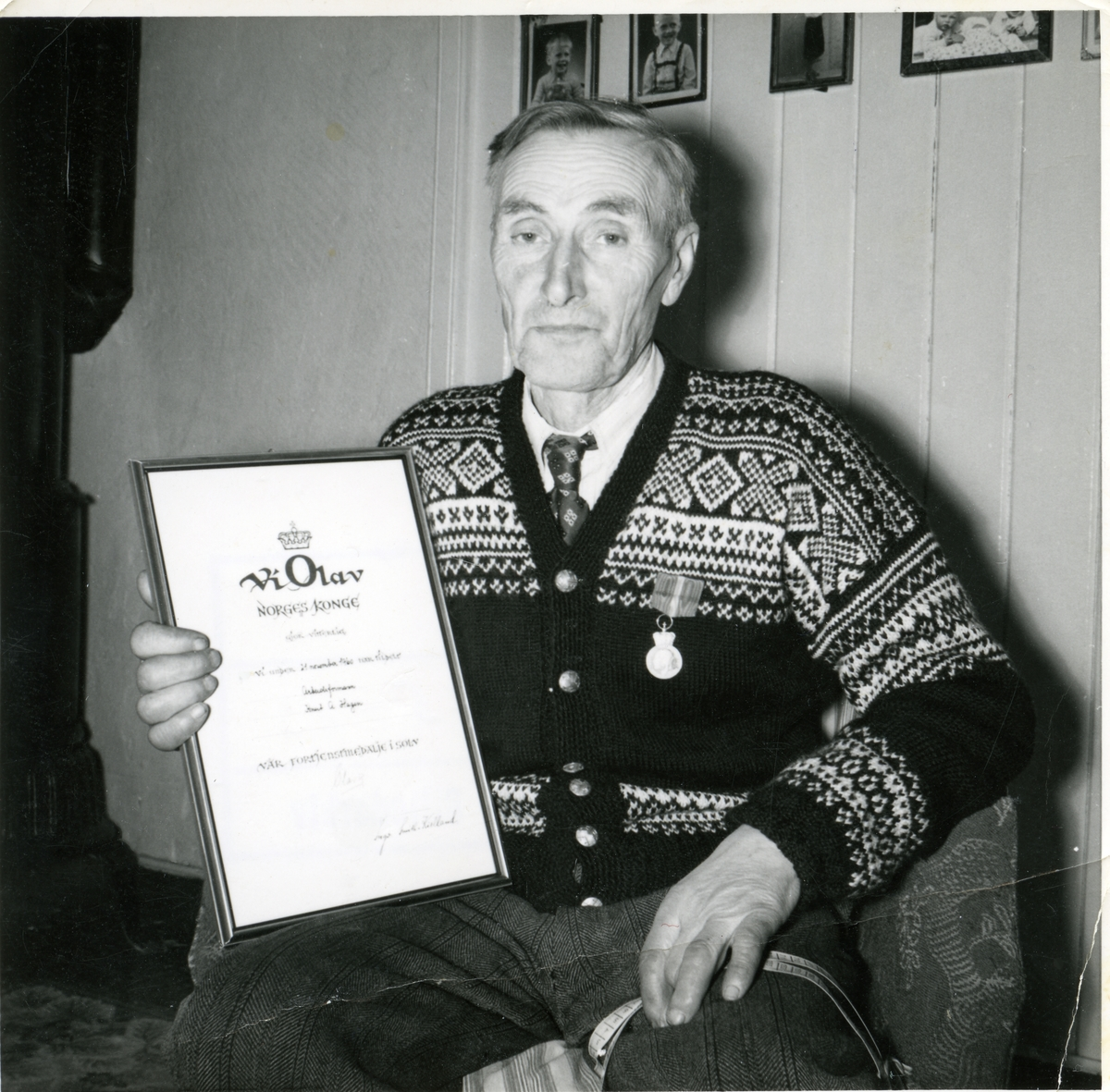 Portrett av Knut Hagen. han holder et diplom og han har fortjenestemedlajen på brystet.