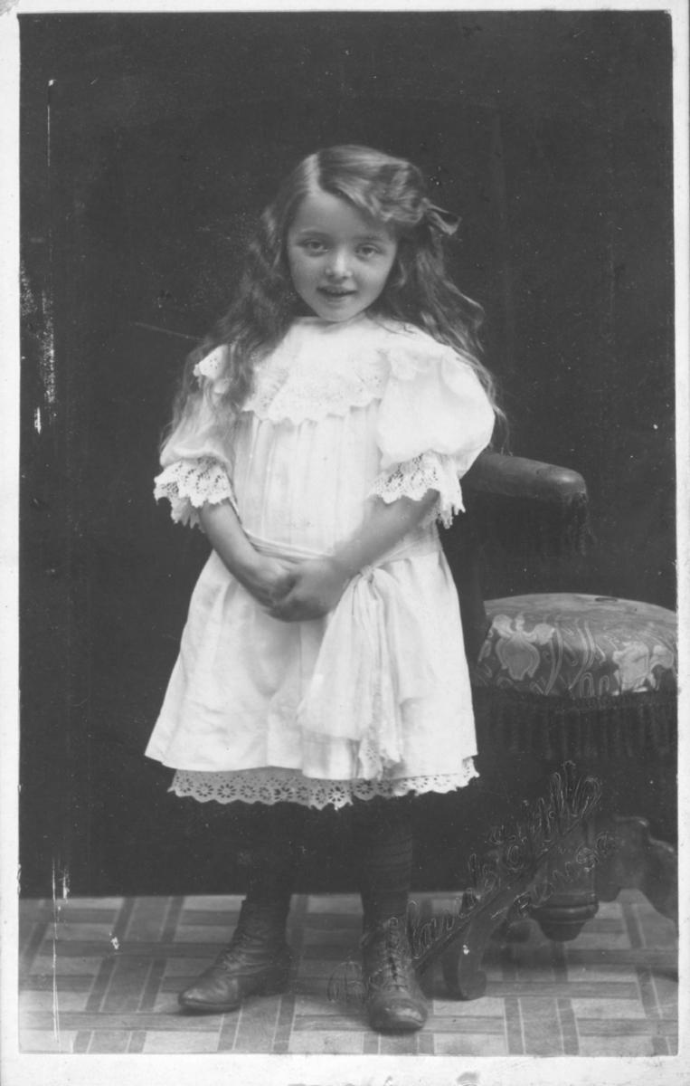 Visittkortportrett av en jente i hvit kjole.