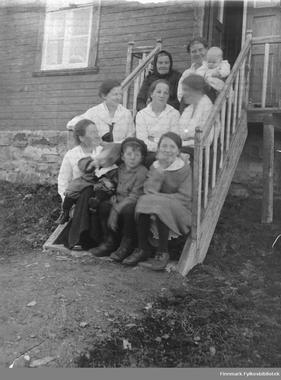 Gruppebilde av kvinner og barn sittende i ei trapp i Kjelsvik, ca. 1900? Påskrift bak på bildet: 'Fra Kjelsvik. Gustavs hus. Bestemor Fikse' - sistnevnte het Maren Dorthea Jakobsdatter Fikse, og sitter øverst til høyre. B 5729
