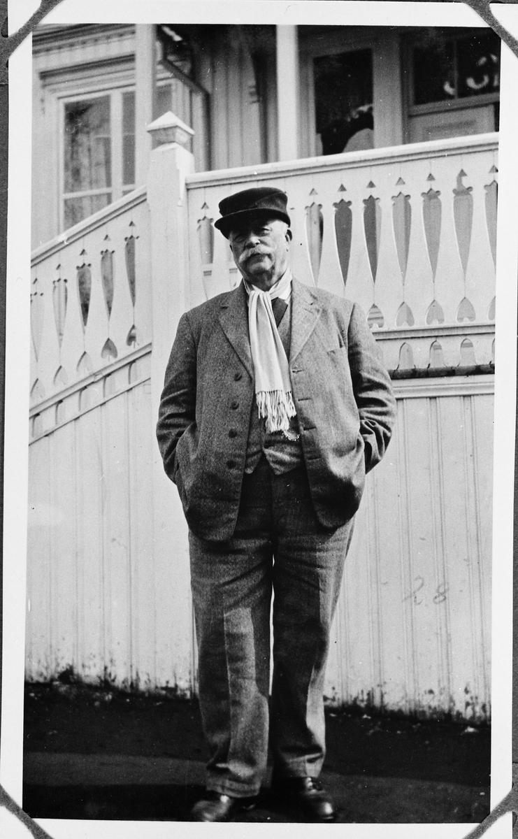Helfigurs portrett av sogneprest Anders Hovden. Trolig fotografer på hagesida av hovedbygningen i prestegården. Året er 1931.