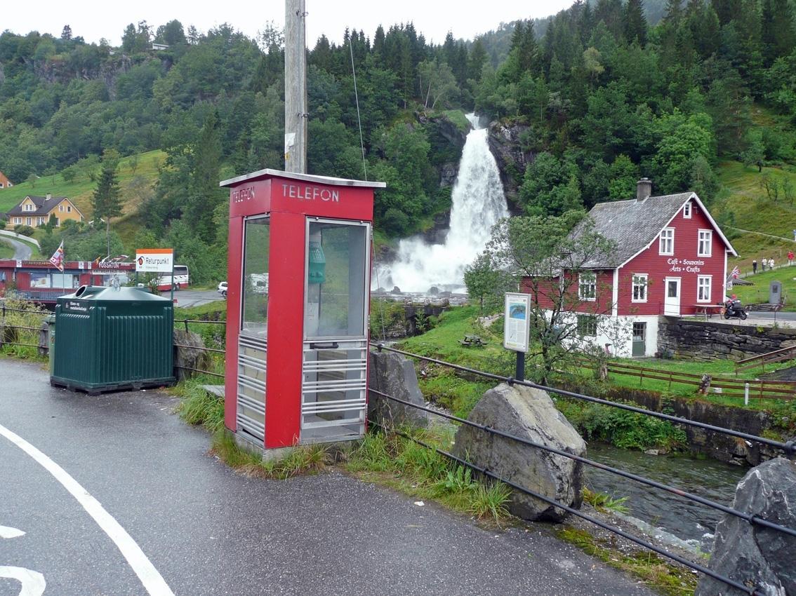 Telefonkiosken står ved Steindalsfossen i Nordheimsund, og er en av 100 vernede telefonkiosker i Norge. De røde telefonkioskene ble laget av hovedverkstedet til Telenor (Telegrafverket, Televerket). Målene er så å si uforandret.  Vi har dessverre ikke hatt kapasitet til å gjøre grundige mål av hver enkelt kiosk som er vernet.  Blant annet er vekten og høyden på døra endret fra tegningene til hovedverkstedet fra 1933. Målene fra 1933 var: Høyde 2500 mm + sokkel på ca 70 mm Grunnflate 1000x1000 mm. Vekt 850 kg. Mange av oss har minner knyttet til den lille røde bygningen. Historien om telefonkiosken er på mange måter historien om oss.  Derfor ble 100 av de røde telefonkioskene rundt om i landet vernet i 1997. Dette er en av dem.
