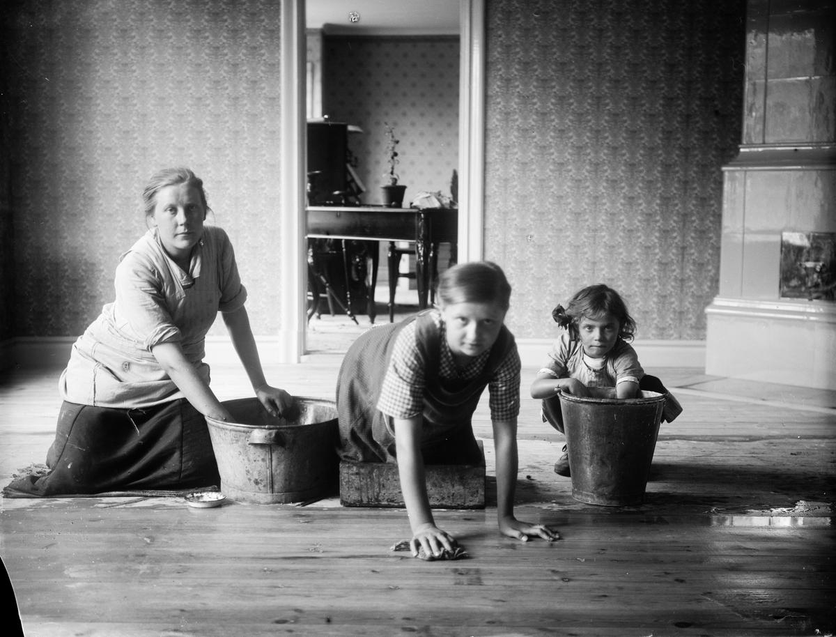 Sannolikt Helmy och Helga Melberg som skurar golv tillsammans med sin mor Frida Melberg, Altuna socken, Uppland 1918
