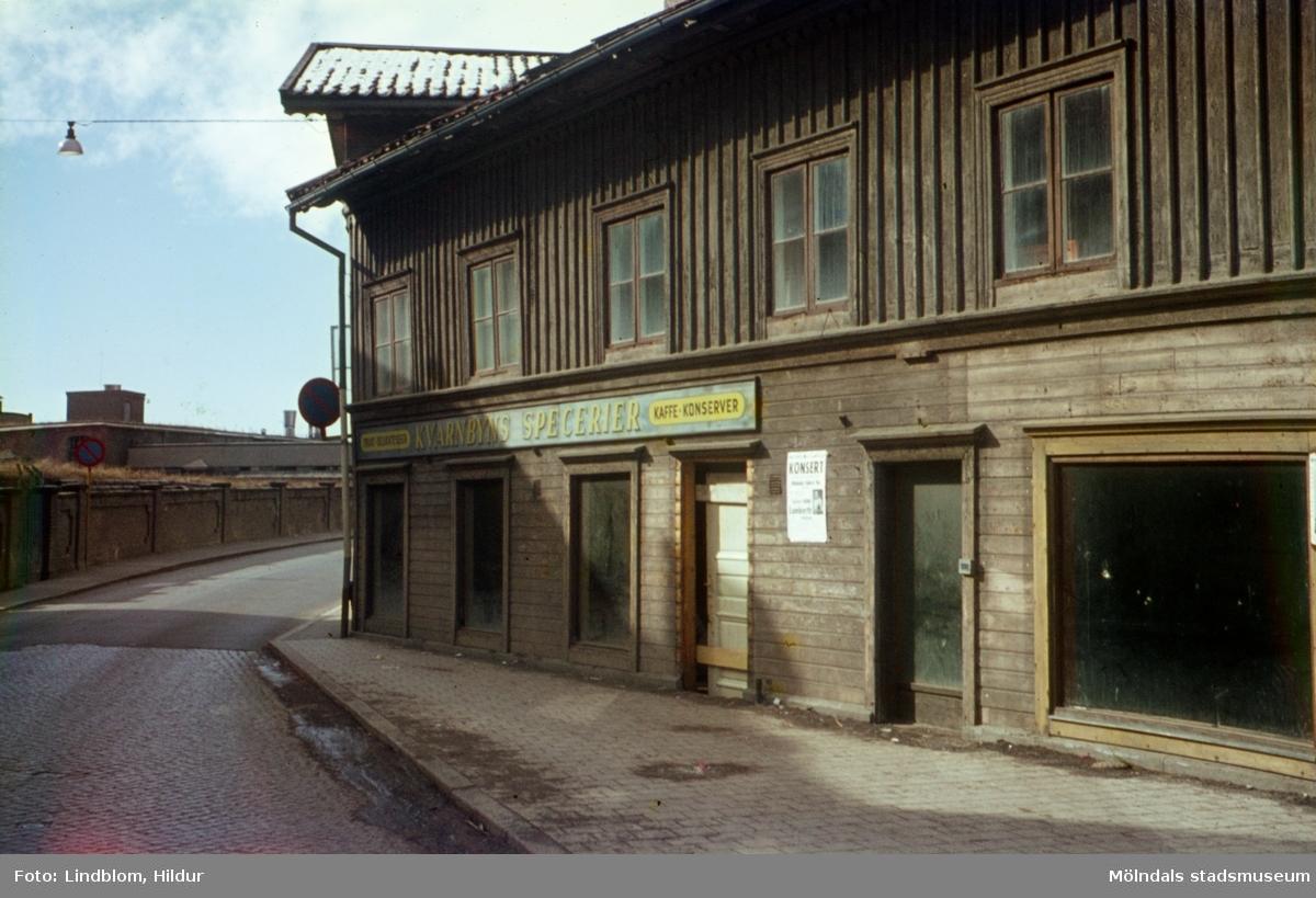 """Kvarnbygatan vid Gamla Torget i Mölndal, ca 1962. På vänster sida av gatan ses Papyrus mur, på höger sid ses huset Kvarnbygatan 39, Nunstedts Speceriaffär. På fasaden sitter en affärsskylt med texten """"Kvarnbyns Specerier"""".  För mer information om bilden se under tilläggsinformation."""