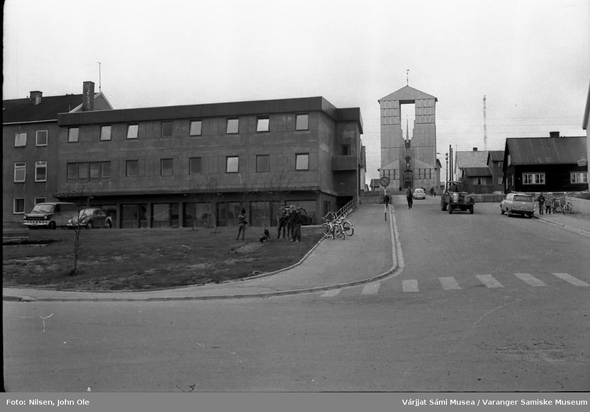 Gatebilde fra Vadsø sentrum, hotellbygningen til venstre og Vadsø kirke øverst i bildet. En traktor med blant annet melkespann på hengeren er på vei opp bakken. 1967.